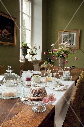 A long breakfast table with cake on a cake stand and under a glass cloche in a a traditional dining room with green-painted walls