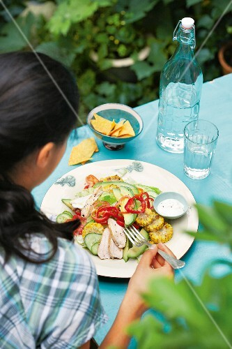 A woman eating and Mexican salad with sweetcorn and chicken breast fillets