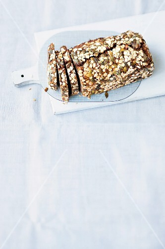 A sliced loaf of communal bread on a chopping board