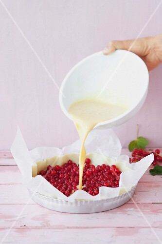 Cream topping being poured over a redcurrant tart