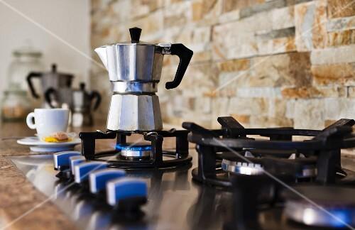 An espresso jug on a gas hob