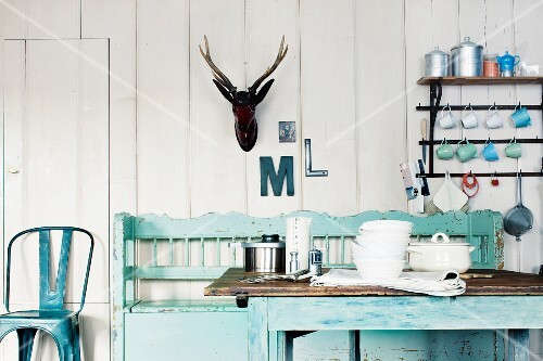 A country house style kitchen with a bench, a table, a wall shelf and antlers on the wall