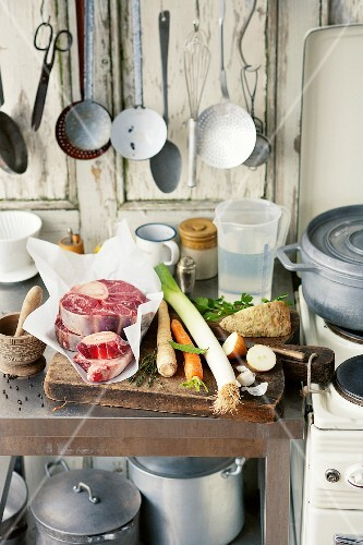 Ingredients for beef broth on a kitchen work surface next to a stove in a country house-style kitchen