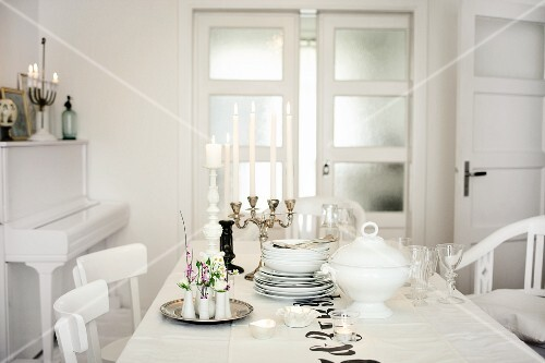 The table with flower arrangements, candle holders and festive soup crockery