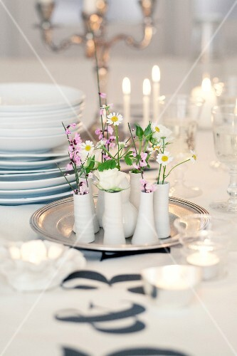 Flowers in small vases on a tray as table decoration