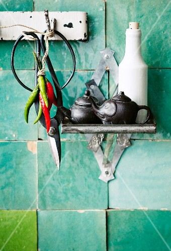 Scissors, chillies & various vessels on kitchen wall