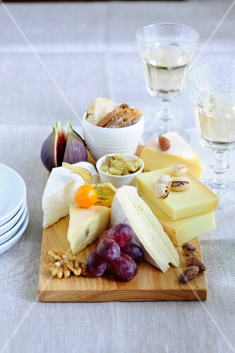A cheese platter with fruit, nuts and apple mustard