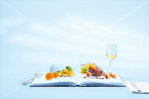 An open pop-up book showing a venison dish