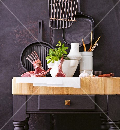 Saddle of lamb, kitchen utensils and ingredients on a kitchen counter