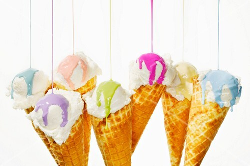 Various different colours of nail polish being poured onto ice cream cones