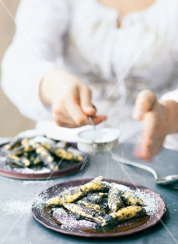 Handmade poppyseed pasta being dusted with icing sugar