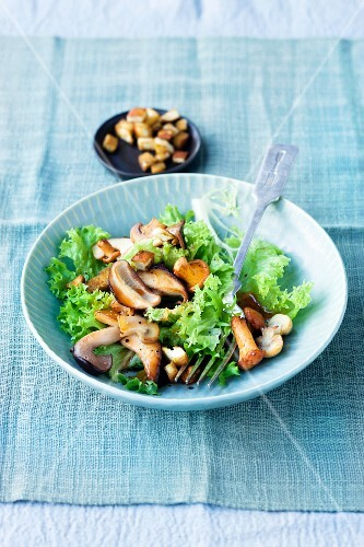 Frisee lettuce with mushrooms and pretzel croutons