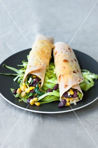 Enchiladas with spinach, sweetcorn and black beans on iceberg lettuce
