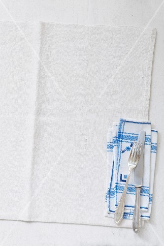 Cutlery and napkins on a linen cloth (seen above)