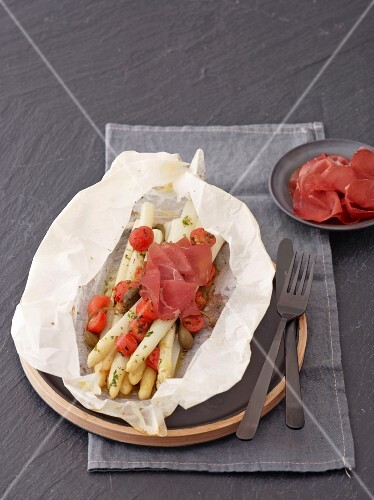 White asparagus with cherry tomatoes, capers and bresaola on parchment paper