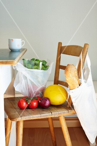 Groceries in bags and on a wooden chair