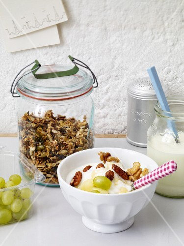 Yogurt with grapes and nuts with a jar of crunchy muesli in the background