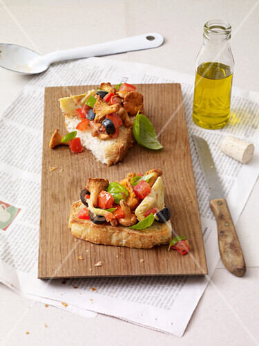 Bruschetta topped with chanterelle mushrooms, olives, artichokes and tomatoes