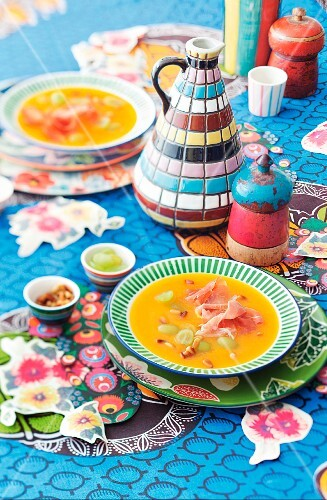 Carrot and grape soup on a colourfully decorated table