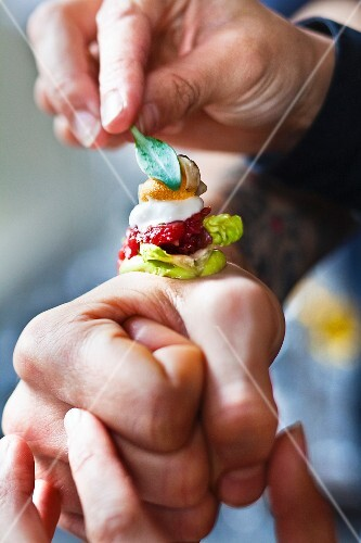 A canapé with oyster and tatar being served on the back of someone's hand at the restaurant De Librije (Netherlands)