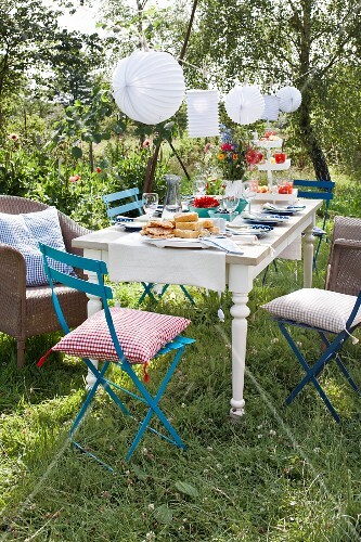 A table laid in a summer garden decorated with lanterns