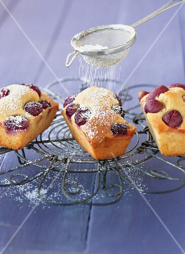 Mini grape cakes being dusted with icing sugar