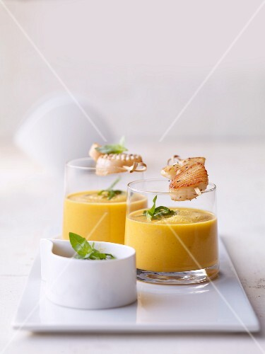 Glasses of lime and carrot soup with scallops on skewers