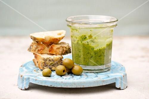 A jar of salsa verde, green olives and sliced of bread