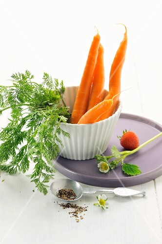 Fresh carrots in a cup with a strawberry and pepper