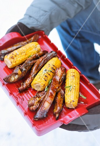 Grilled spare ribs and corn cobs on a red tray