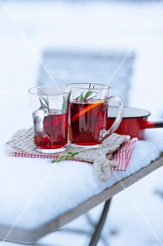 Glasses of mulled wine garnished with orange slice in the snow