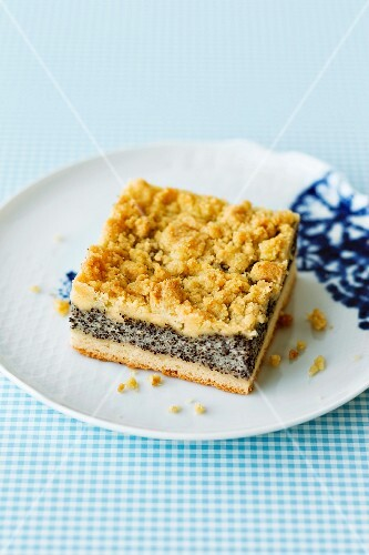 A slice of poppy seed crumble cake on a plate