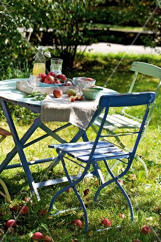 Apples and apple juice on a table in a summer garden