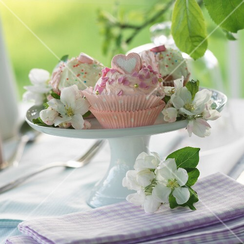 Various cakes decorated with apple blossom on a cake stand