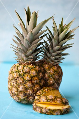 A whole pineapple and pineapple slices