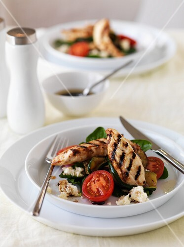 Grilled chicken strips on a bed of vegetables salad with sheep's cheese
