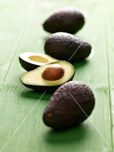 Avocados, whole and halved, on a green wooden surface