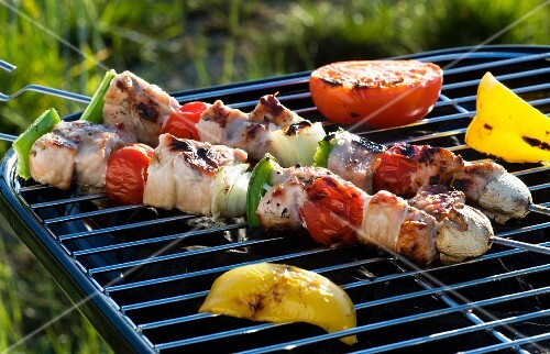 Pork kebabs, pepper and tomatoes on a barbecue