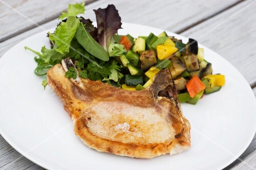 Grilled pork chop with a side of vegetables and a mixed leaf salad