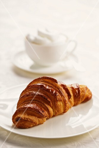 A croissant on a plate with a cappuccino in the background