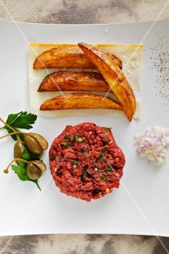 Beef tatar with potato wedges and capers