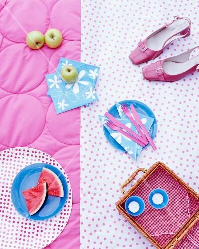 A picnic basket, fruit, napkins and shoes on a rug