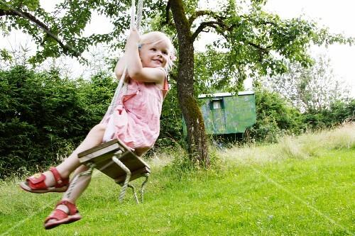 Blond girl on a garden swing