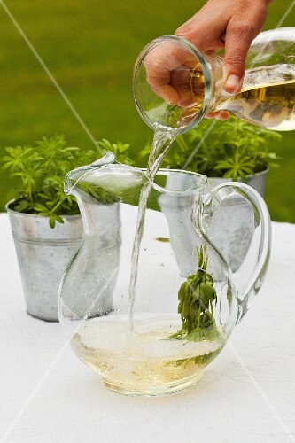White wine being poured into a jug of woodruff