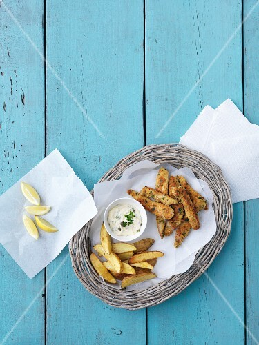 Fish fillets with a parmesan and lemon coating a potato wedges (seen from above)