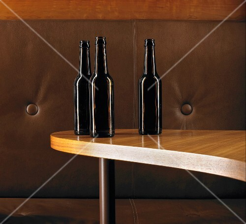 Three brown glass bottles on kidney-shaped table in front of leather sofa