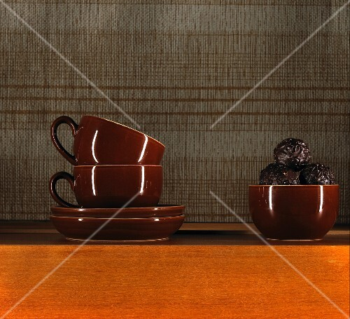 Chocolates in brown cup and two stacked coffee cups