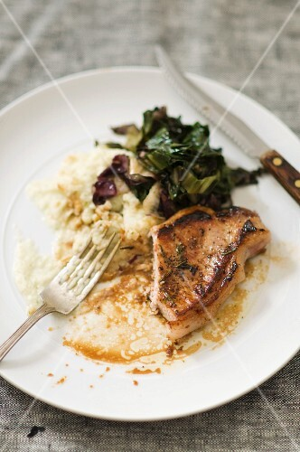 Partially Eaten Pork Chop with Mashed Potato and Braised Greens