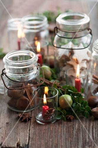 Cinnamon stars, chestnuts and cinnamon sticks in jars between candles