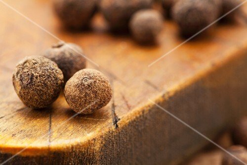 Allspice berries on a chopping board (close-up)
